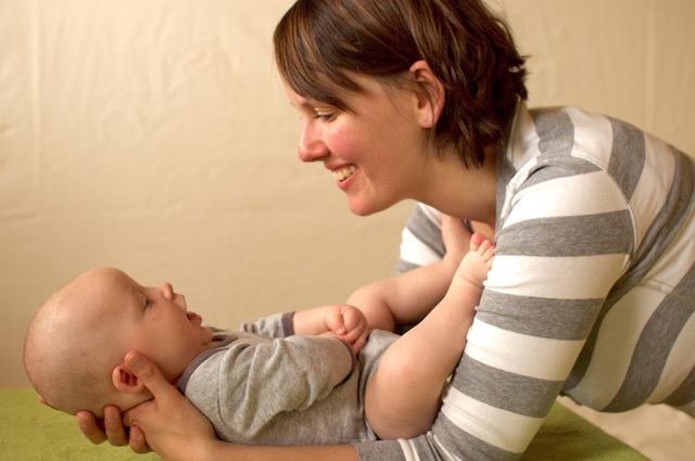 Die Mutter hält ihr Baby in ihren Armen und lächelt es dabei an