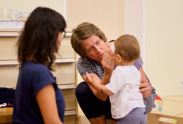 Die Erzieherin putzt dem Kleinkind die Nase