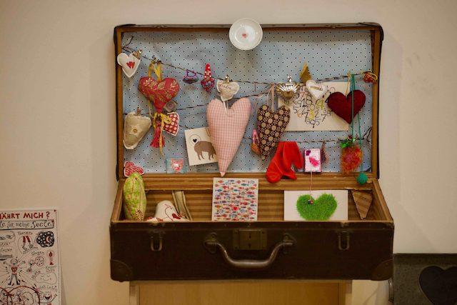 Geöffneter Koffer, der dekoriert ist mit Stoffherzen, Karten und anderen Kleinigkeiten