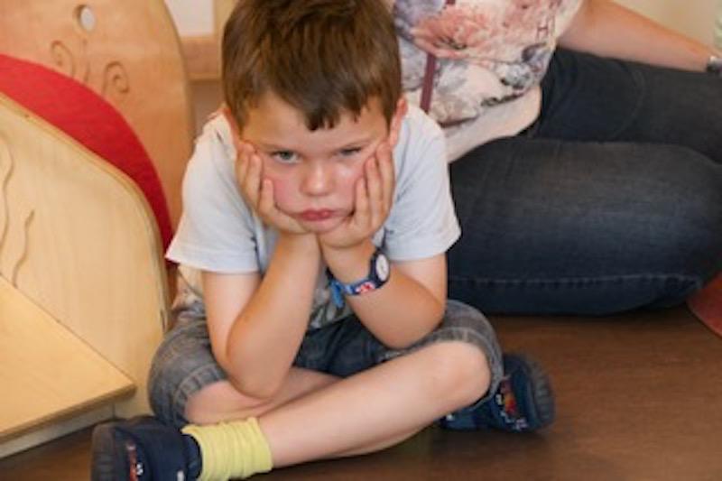 Junge sitzt frustriert am Boden